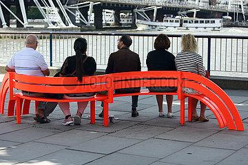 London  Grossbritannien  Menschen sitzen an der Themse auf einer roten Bank