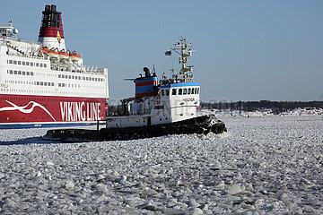 Helsinki  Finnland  Faehre der Viking Line und Schlepper Hector auf der gefrorenen Ostsee