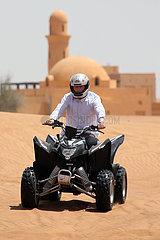Dubai  Vereinigte Arabische Emirate  Jugendlicher faehrt auf einem Quad durch die Wueste