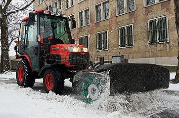 Berlin  Deutschland  Winterdienst befreit einen Gehweg vom Schnee