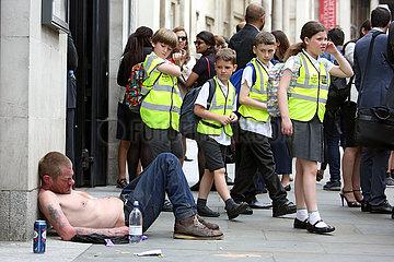 London  Grossbritannien  Schulkinder laufen an einem auf der Strasse schlafenden Obdachlosen vorbei