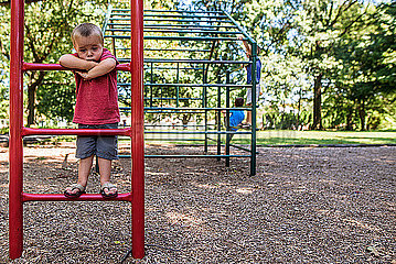 Toddler boy looking sad on playground ladder with older boys playing