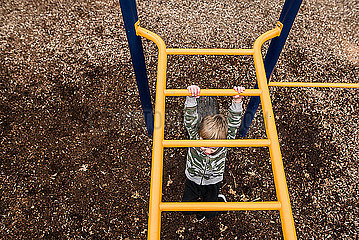 looking down from above at young boy going across monkey bars at park