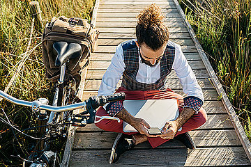 Well dressed man sitting on a wooden walkway in the countryside next to a bike with cell phone and laptop