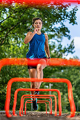 Young woman jumping over hurdles on a woodchip trail