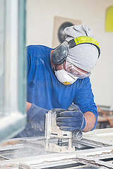 Glazier sanding window pane
