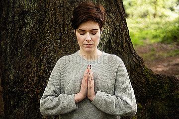 Woman practising Reiki  large tree trunk in background