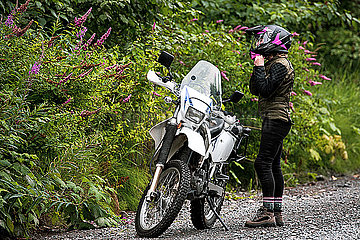 A women takes a break from motorcycle riding and takes off her helmet.