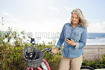 Senior woman using mobile phone while standing by bicycle against sea during sunny day