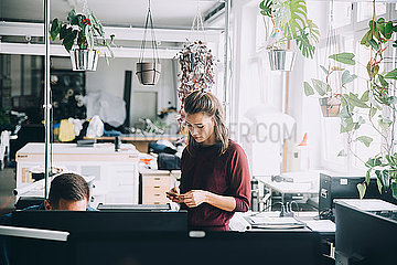 Businesswoman using mobile phone while standing by male colleague in creative office