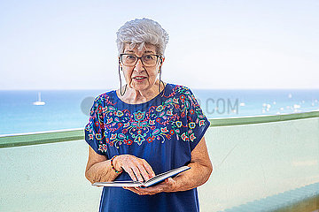 Senior woman reading a book on a terrace