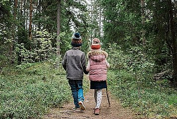 brother and sister holding hands walking through the forest in fall