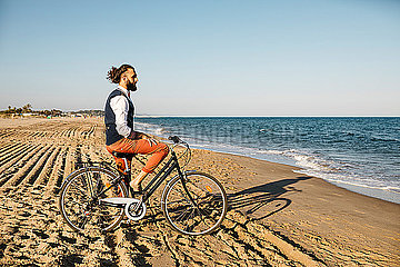 Well dressed man with his bike on a beach