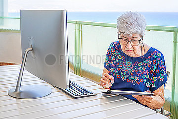 Senior woman using computer on the terrace