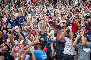 Singapur  Republik Singapur  Menschen beobachten die ringfoermige Sonnenfinsternis