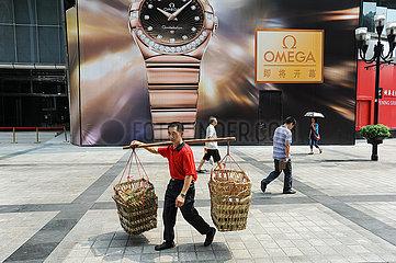 Chongqing  China  Ein Traeger  auch Bang-Bang-Man genannt  traegt eine Bambusstange mit Koerben auf seiner Schulter