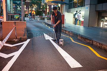 Singapur  Republik Singapur  Arbeiter streicht den Pfeil einer Strassenmarkierung an