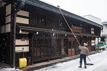 Takayama  Japan  Mann beseitigt Schnee von einem Hausdach