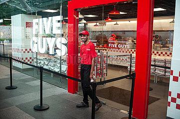 Singapur  Republik Singapur  Mitarbeiter vor Restaurant der Five Guys Burgers and Fries Burgerkette