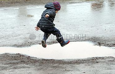 Magdeburg  Deutschland  Junge springt in eine Pfuetze