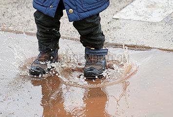 Magdeburg  Deutschland  Detailaufnahme: Kind springt in einer Pfuetze herum