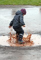 Magdeburg  Deutschland  Junge springt in einer Pfuetze herum