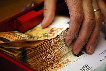 Halle (Saale)  Deutschland  Hand greift nach 50-Euroscheinen in einer Geldkassette