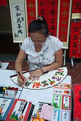 Singapur  Republik Singapur  Eine Kalligraphin verziert einen Handfaecher mit chinesischen Schriftzeichen und Bildern