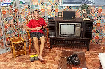 Singapur  Republik Singapur  Aelterer Mann schlaeft auf einem Stuhl und hoert Musik