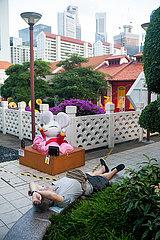 Singapur  Republik Singapur  Mann schlaeft in einem kleinen Park in Chinatown