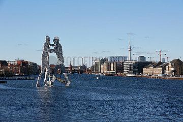 Berlin  Deutschland - Stadtansicht von Friedrichshain und Kreuzberg am Osthafen. Die Skulptur Molecule Men im Vordergrund.