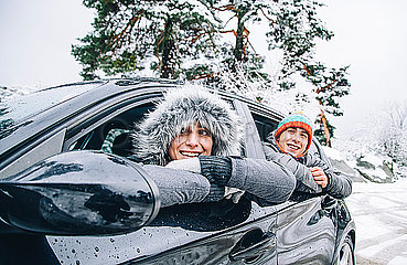 Portrait of happy young couple sitting in a car in winter forest having fun