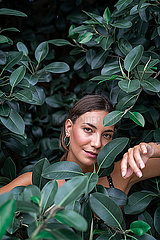 Portrait of young woman among green leaves