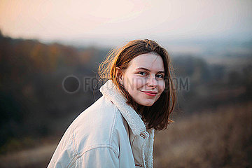 Portrait of a beautiful young woman in warm clothes during sunset