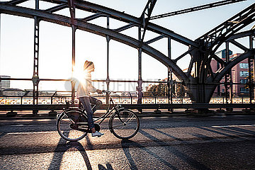Young cyclist on a bridge at sunset