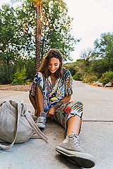 Laughing young woman sitting on slab in a park putting on shoe