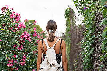 Back view of young woman with backpack strolling in a park