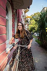 Junge Frau schiebt Fahrrad in Stadt