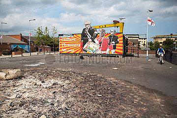 Grossbritannien  Belfast - Proestantisches Plakat am Dr Pitt Memorial Park in East Belfast  vorne Reste vom nach dem bonfire am Orangemens Day
