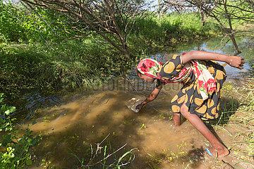 Burferedo  Somali Region  Aethiopien - Maedchen schoepft Wasser aus einem Fluss