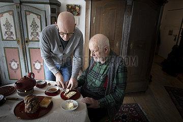 Mann hilft dem alten Vater ein Brot zu schmieren