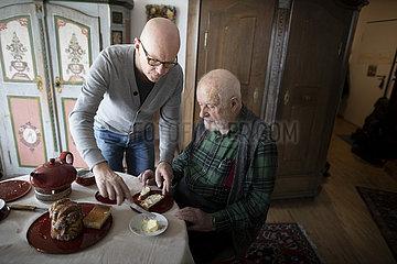 Sohn hilft dem alten Vater ein Brot zu schmieren