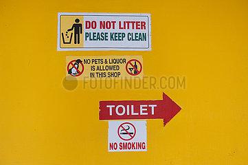 Singapur  Republik Singapur  Verschiedene Verbotsschilder kleben an gelber Hauswand