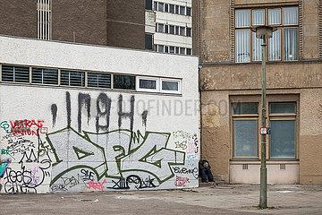 Mann sitzt zusammengekauert in einer Hausecke am Alexanderplatz in Berlin-Mitte