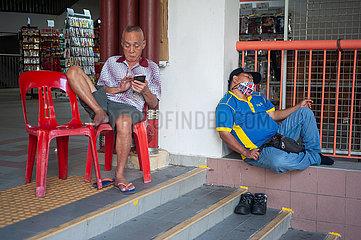 Singapur  Republik Singapur  Zwei Maenner ruhen sich in Chinatown aus