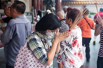 Singapur  Republik Singapur  Frau mit Mundschutz betet in einem buddhistischen Tempel