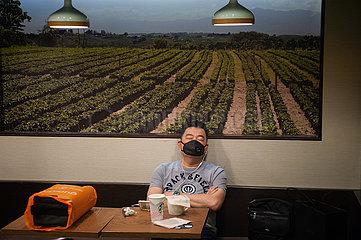 Singapur  Republik Singapur  Mann mit Mundschutz schlaeft in einem Cafe