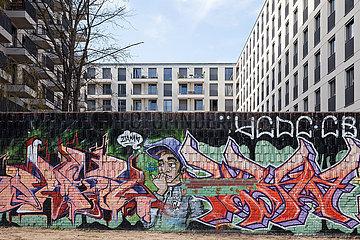 Reste einer Grundstuecksmauer mit Graffiti vor dem Neubau eines Wohngebaeudes auf dem ehemaligen Mauerstreifen an der East-Side-Gallery in Berlin-Friedrichshain