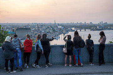 Jugendliche blicken von einer Aussichtsplattform auf Kiew und den Dnepr