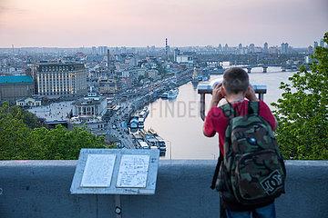 Junge blickt durch Fernrohr von einer Aussichtsplattform auf Kiew und den Dnepr